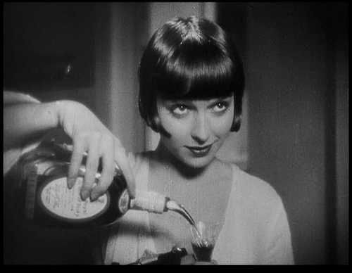 More often than not Louise Brooks smiles, a departure from Theda Bara's vamp image. Here she sweetly pours a drink for her stressed out lover.